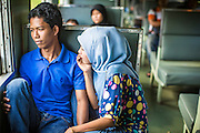 27 OCTOBER 2012 - SUNGAI KOLOK, NARATHIWAT, THAILAND:     A Muslim couple in a third class passenger compartment on a northbound train out of Sungai Kolok, Thailand. Sungai Kolok has been a center of extremist violence. Several car bombs have been detonated in the city, which is on the Malaysian border and very popular with Malaysian tourists. More than 5,000 people have been killed and over 9,000 hurt in more than 11,000 incidents, or about 3.5 a day, in Thailand's three southernmost provinces and four districts of Songkhla since the insurgent violence erupted in January 2004, according to Deep South Watch, an independent research organization that monitors violence in Thailand's deep south region that borders Malaysia.   PHOTO BY JACK KURTZ