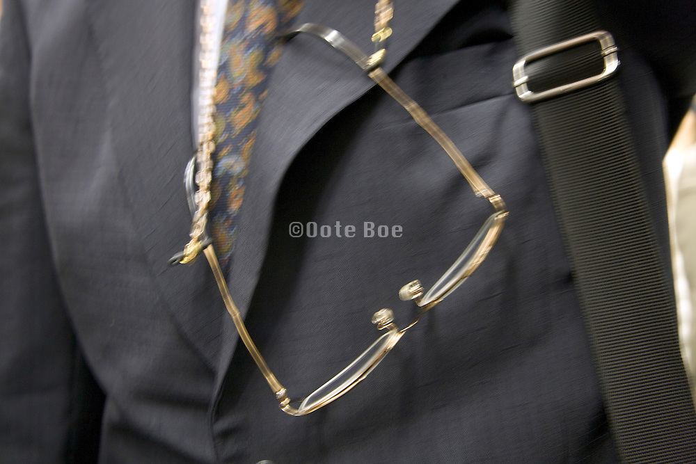 close up of a businessman with reading glasses hanging from his neck