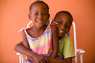 A young boy holds his little sister on his lap in Gaborone, Botswana.