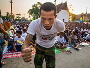 """07 MARCH 2015 - NAKHON CHAI SI, NAKHON PATHOM, THAILAND:  A man channeling the power of his spiritual tattoo goes to the stage at the Wat Bang Phra tattoo festival. Wat Bang Phra is the best known """"Sak Yant"""" tattoo temple in Thailand. It's located in Nakhon Pathom province, about 40 miles from Bangkok. The tattoos are given with hollow stainless steel needles and are thought to possess magical powers of protection. The tattoos, which are given by Buddhist monks, are popular with soldiers, policeman and gangsters, people who generally live in harm's way. The tattoo must be activated to remain powerful and the annual Wai Khru Ceremony (tattoo festival) at the temple draws thousands of devotees who come to the temple to activate or renew the tattoos. People go into trance like states and then assume the personality of their tattoo, so people with tiger tattoos assume the personality of a tiger, people with monkey tattoos take on the personality of a monkey and so on. In recent years the tattoo festival has become popular with tourists who make the trip to Nakorn Pathom province to see a side of """"exotic"""" Thailand.  PHOTO BY JACK KURTZ"""
