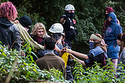 An HS2 Rebellion activist is carried away by a fellow activist after being injured whilst National Eviction Team enforcement agents were trying to prevent direct action to interrupt tree cutting in conjunction with the HS2 high-speed rail link in Denham Country Park on 7 September 2020 in Denham, United Kingdom. Anti-HS2 activists continue to try to prevent or delay works on the controversial £106bn project for which the construction phase was announced on 4th September from a series of protection camps based along the route of the line between London and Birmingham.