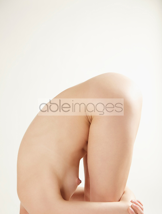Profile of a nude woman bending over her knees, headless