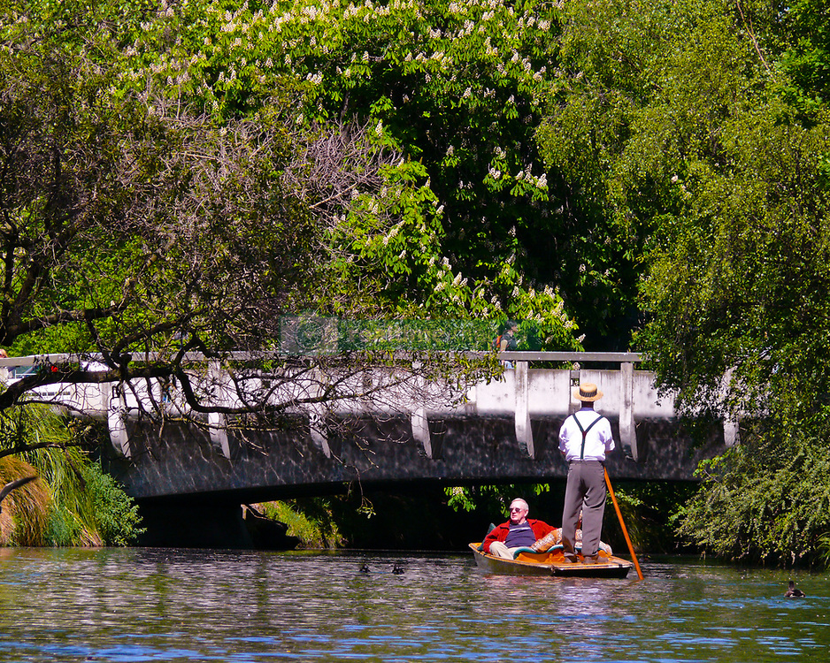 Oct 30, 2008 - Christchurch, South Island, New Zealand - Edwardian-garbed punter, complete with straw boater hat,  guides his punt under a low bridge as he smoothly glides tourists past the leafy banks of the Avon River aboard elegant Cambridge-style punts. No visit to Christchurch is complete without this relaxed and tranquil iconic experience. The punter stands at the stern of the flat-bottomed boat propelled by a pole and performs a series of maneuvers requiring expertise, not simply pushing a punt around on the water. (Credit Image: © Arnold Drapkin/ZUMA Press)