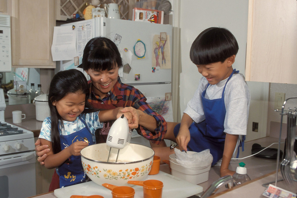 Asian-American boy (7) and girl (6) measure and mix cake ingredients with Asian mother at home in kitchen in Austin, Texas. Model Release.<br /> ©Bob Daemmrich