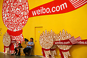 Two exhibition employees sit by signs for Sina's Weibo.com, China's most popular micro-blogging service, at the ChinaJoy Expo, the annual online gaming expo, in Shanghai, China on 30 July, 2011.   China is now the world's largest online gaming market, contributing one-third to the global revenue in this sector in 2009, or 56 percent of the Asia Pacific total. With over 100 million subscribers, Weibo, China's own twitter-like micro blog social network service from Sina.com has become a rare platform for Chinese netizens to voice their discontent  as well as exposing corruption. So much so that the central government has recently required all users to register with their real names in hopes of increasing its censorship.