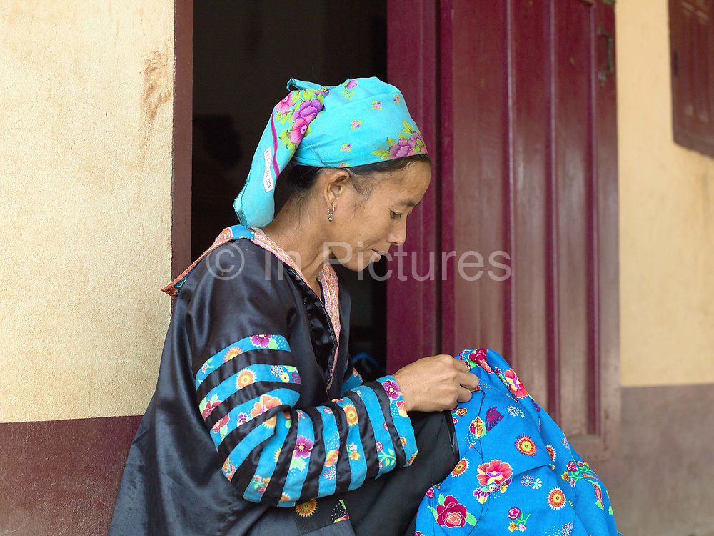 An Hmong ethnic minority woman sewing her traditional costume outside her home in the newly relocated village of Ban Chalern, Phongsaly province, Laos. Ban Chalern was relocated due to construction of the Nam Ou Cascade Hydropower Project Dam 7