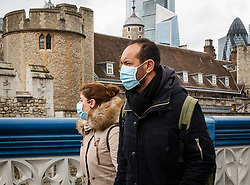 © Licensed to London News Pictures. 14/03/2020. London, UK. Tourists wearing medical masks walk across Tower Bridge near the Tower of London this afternoon. The coronavirus is continuing to spread across Europe and the UK and today Spain is reportedly in lockdown for all non essential travel. Photo credit: Vickie Flores/LNP