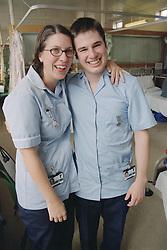 Student nurses on medical ward standing together smiling,