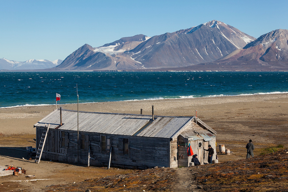 Men stand outside the main barracks building at Calypsobyen, Svalbard, site of a coal mining operation erected by the British Northern Exploration Company in the early 1900s. Polish researchers have used the site for field operations every summer since 1986.
