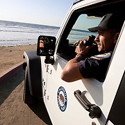 """Ed Vodrazka, 50, feels he'll be hearing a call come in over the radio any day now announcing a capsized boat with over twenty undocumented migrants in the heavy surf off of Torrey Pines State Beach. As a lieutenant lifeguard at Torrey Pines State Beach , Vodrazka would be the first to respond. He has seen four boats wash ashore and keeps a vigilant watch for others. For more images, search for """"immigration by air and sea"""". Please contact Todd Bigelow directly with your licensing requests."""