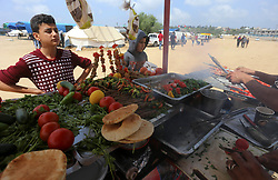 April 27, 2018 - Bureij, Gaza Strip - A Palestinian man prepares chicken Grill during clashes with Israeli security forces during tents protest demanding the right to return to their homeland, in Bureij in the cetner of Gaza strip on April 27, 2018  (Credit Image: © Yasser Qudih/APA Images via ZUMA Wire)