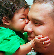 Six-month-old Carlos Jr. plants a kiss on his father, Carlos Serrano.