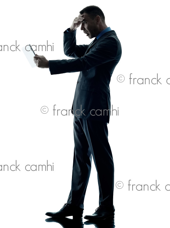one caucasian business man standing using digital tablet  surprised silhouette isolated on white background