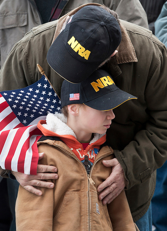 """Gun rights supporter Kenny Deal of Stafford, Conn., hugs his son Daniel, at rally at the Capitol in Hartford, Conn., Saturday, Jan. 19, 2013.  The rally, dubbed, """"Guns Across America"""", at Connecticut's state Capitol and state capitol buildings across the country to raise concerns about possible new gun legislation that could affect gun owners' rights in the wake of the Dec. 14 school shooting at Sandy Hook Elementary School in Newtown. (AP Photo/Jessica Hill)"""