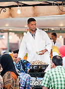 A man selling escargot, cooked snails, from his stall in the Djemaa el Fna in the medina of Marrakech, Morocco. Every night the main square fills with dozens of food vendors and their carts.