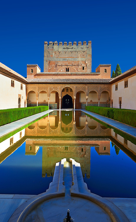 """Arabesque Moorish architecture and pond of the  Court of the Myrtles  of the Palacios Nazaries,  Alhambra. Granada, Andalusia, Spain. . The Alhambra is a palace and fortress complex located in Granada, Andalusia, Spain. It was originally constructed as a small fortress in 889 CE on the remains of ancient Roman fortifications. The Alhambra was renovated and rebuilt in the mid-13th century by the Arab Nasrid emir Mohammed ben Al-Ahmar of the Emirate of Granada, who built its current Alhambra palace and walls. The Alhambra was converted into a royal palace in 1333 by Yusuf I, Sultan of Granada. The decoration of The Alhambra consists for the upper part of the walls, as a rule, of Arabic inscriptions—mostly poems by Ibn Zamrak and others praising the palace—that are manipulated into geometrical patterns with vegetal background set onto an arabesque setting (""""Ataurique""""). Much of this ornament is carved stucco (plaster) rather than stone. Tile mosaics (""""alicatado"""") of The Alhambra, with complicated mathematical patterns (""""tracería"""", most precisely """"lacería""""), are largely used as panelling for the lower part. .<br /> <br /> Visit our SPAIN HISTORIC PLACXES PHOTO COLLECTIONS for more photos to download or buy as wall art prints https://funkystock.photoshelter.com/gallery-collection/Pictures-Images-of-Spain-Spanish-Historical-Archaeology-Sites-Museum-Antiquities/C0000EUVhLC3Nbgw <br /> .<br /> Visit our ISLAMIC HISTORICAL PLACES PHOTO COLLECTIONS for more photos to download or buy as wall art prints https://funkystock.photoshelter.com/gallery-collection/Islam-Islamic-Historic-Places-Architecture-Pictures-Images-of/C0000n7SGOHt9XWI"""