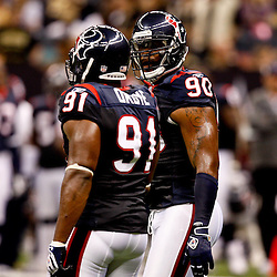 August 21, 2010; New Orleans, LA, USA; Houston Texans defensive end Mario Williams (90) talks with defensive tackle Amobi Okoye (91) during the first quarter of a preseason game at the Louisiana Superdome. Mandatory Credit: Derick E. Hingle