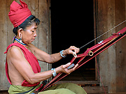 A Kayah Red Karen ethnic minority woman weaving a head-cloth on a traditional back-strap loom on 22nd March 2016 in Kayah State, Myanmar. Myanmar is one of the most ethnically diverse countries in Southeast Asia with 135 different indigenous ethnic groups with over a dozen ethnic Karenni subgroups in the Kayah region. Kayah women wear a simple red tunic worn with a broad white sash decorated with coloured tassles and a striped hand-woven head-cloth