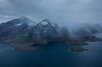 Spring snow stom passes over mountains of Lofotodden national park above Selfjord, Moskenesøy, Lofoten Islands, Norway
