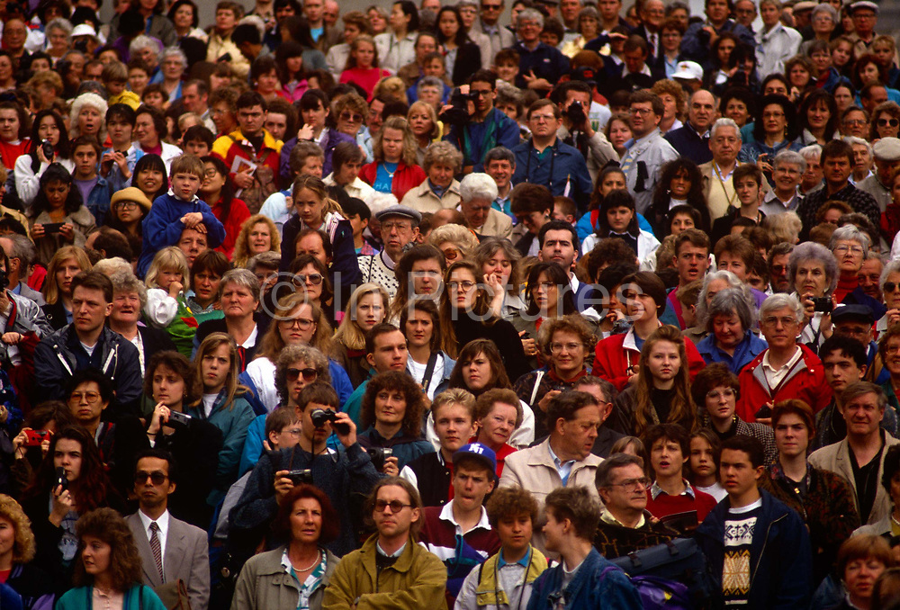 A crowd of workers listen to speeches by their trade union during a council strike in Liverpool. A sea of faces looks towards us, their expressions serious and concerned at the loss of their jobs and livelihoods. Their trade union has organised this meeting out in the open air in the city centre, a protest against unfair reduction of earnings and an erosion of working conditions. These people are English Liverpool council workers recently made redundant and have gathered in the city centre to express their willingness to act againist their former-employers.