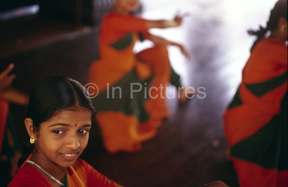 "Girls practice Mohiniyattam (also spelled Mohiniattam), Kerala's sole classical dance for women.<br /> The dance literally means ""dance of the enchantress"" and had all but disappeared before it was reintroduced at the Kerala Kalamadalam.<br /> The Kalamandalam was founded in 1930 to preserve the cultural traditions of Kathakali, the stylised dance drama of Kerala. Kathakali is the classical dance-drama of Kerala, South India, which dates from the 17th century and is rooted in Hindu mythology. Kathakali is a unique combination of literature, music, painting, acting and dance performed by actors wearing extensive make up and elaborate costume who perform plays which retell in dance form stories from the Hindu epics."