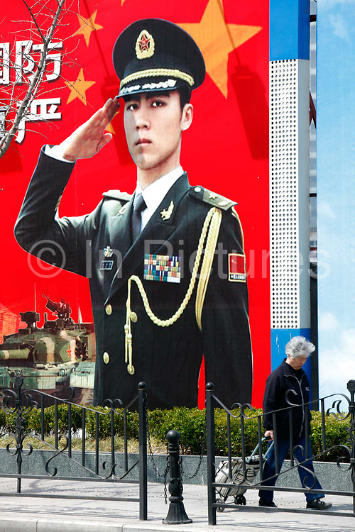 A pedestrian walks past a large poster showing saluting Chinese People's Liberation Army (PLA) soldiers in Shanghai, China, on 01 April 2011.  In its recently released national defense white paper, China has tried to praise its military modernization while assuring foreign countries, especially the United States, that its build ups are not geared toward expansionism and regional dominance.