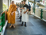 """29 NOVEMBER 2016 - BANGKOK, THAILAND:  Buddhist monks wait to start a """"tak bat"""" or merit making ceremony in the Ratchaprasong skywalk of the Bangkok BTS system. The tak bat was to honor Bhumibol Adulyadej, the Late King of Thailand. Food and other goods were given to the monks, who in turn gave the items to charities that will distribute them to Bangkok's poor. More than 100 Buddhist monks participated in the merit making ceremony. The ceremony was organized by the merchants in the Ratchaprasong Intersection, which includes some of Bangkok's most upscale shopping centers.     PHOTO BY JACK KURTZ"""