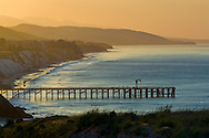 Golden sunrise light over coastal hills, pier, and beach at Gaviota Beach State Park, near Santa Barbara, California