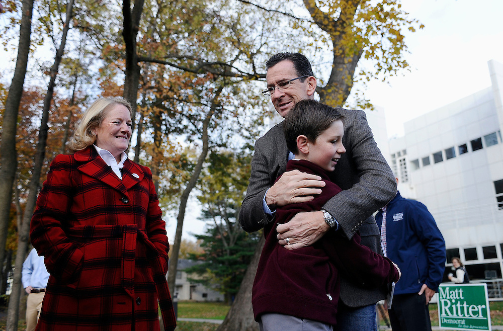 Connecticut Gov. Dannel P. Malloy, right, hugs James Mullarkey, 10, of Hartford who was volunteering at the polls where Malloy and wife, Cathy, left, voted, Tuesday, Nov. 4, 2014, in Hartford, Conn. (AP Photo/Jessica Hill)