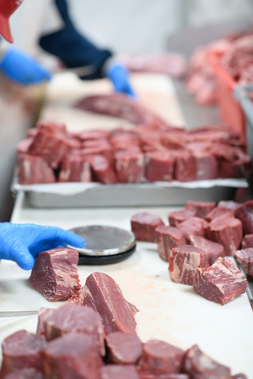 Editorial Images of food workers cutting up beef at a meat processing facility in Florida
