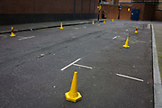 Yellow cones prevent parking in a London side-street. A low, wide angle of the road where the cones are spaced evenly to stop vehicles from parking in these spaces - possibly for nearby filming units. The places that usually allow city cars ample parking opportunities are now restricted and off-limits. The bright yellow cones are highly visible to the otherwise grey road surface.