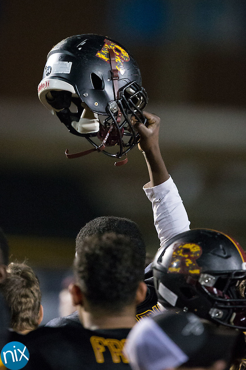 A JM Robinson Bulldogs player holds his helmet high following their loss in the second round of the NCHSAA 3A playoffs at South Iredell High School November 20, 2015, in Statesville, North Carolina.  The Vikings defeated the Bulldogs 14-13.  (Brian Westerholt/Special to the Tribune)