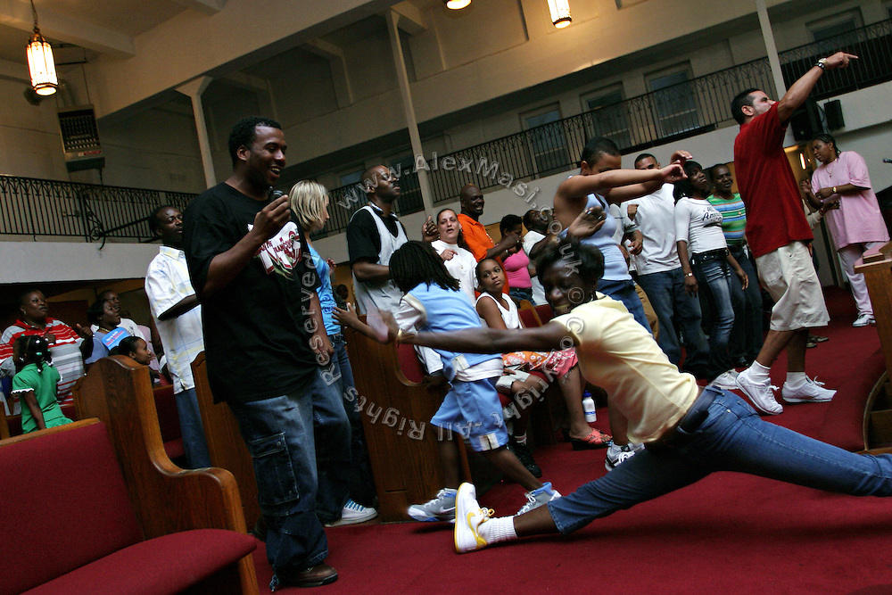 Christian devotees dancing Hip Hop music during a Mass Service at the Hip Hop Church in Harlem, New York, NY., on Thursday, July 21, 2006. A new growing phenomenon in the United States, and in particular in its most multiethnic city, New York, the Hip Hop Church is the meeting point between Hip Hop and Christianity, a place where ?God? is worshipped not according to religious dogmatisms and rules, but where the ?Holy Spirit? is celebrated by the community through young, unique, passionate Hip Hop lyrics. Its mission is to present the Christian Gospel in a setting that appeals to both, those individuals who are confessed Christians, as well as those who are not regularly attending traditional Services, while helping many youngsters from underprivileged neighbourhoods to feel part of a community, to make them feel loved and to help them not to give up when problems arise. The Hip Hop Church is not only forward-thinking but it also has an important impact where life at times can be difficult and deceiving, and where young people can be easily influenced for the worst purposes. At the Hip Hop Church, members are encouraged to sing, dance and express themselves in any way that the ?Spirit of God? moves them. Honours to students who have overcome adversity, community leaders, church leaders and some of the unsung pioneers of Hip Hop are common at this Church. Here, Hip Hop is the culture, while Jesus is the centre. Services are being mainly in Harlem, where many African Americans live; although the Hip Hop Church is not exclusive and people from any ethnic group are happily accepted and involved with as much enthusiasm. Rev. Ferguson, one of its pioneer founders, has developed ?Hip-Hop Homiletics?, a preaching and worship technique designed to reach the children in their language and highlight their sensibilities, while bringing forth Christianity. This ?Keep It Real? evangelism style is the centrepiece of Rev. Ferguson?s ministry, one that speaks the plain language of th