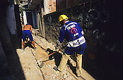 CLOSED SEWERS. Rocinha Favela, Rio de Janeiro, Brazil, South America. Municipal workers closing open sewers. Although Rocinha is technically classified as a neighborhood, many still refer to it as a favela. It developed from a shanty town into an urbanized slum. Today, almost all the houses in Rocinha are made from concrete and brick. Some buildings are three and four stories tall and almost all houses have basic sanitation, plumbing, and electricity. Compared to simple shanty towns or slums, Rocinha has a better developed infrastructure and hundreds of businesses. There is also lots of deliquency, crime and drugs in the favelas.