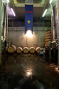 The vat hall with stainless steel fermentation vats and solar symbols. Oak barrels and a flag of Romanin. Chateau Romanin, Saint Remy de Provence, Bouches du Rhone, Provence, France, Europe