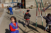 Boys and girls play in a playground associated with their high rise apartment. Electricity and water shortages to urban dwellings mean that people spend as much time outdoors as possible.Pyongyang.<br /> <br /> North Korea<br /> <br /> <br /> <br /> 14 Mar 2004<br /> ©Jeremy Horner
