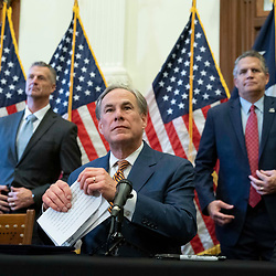 Texas Gov. Greg Abbott (c) with legislators and energy officials, signs two bills strengthening the Texas power grid and infrastructure that were emergency items on his legislative agenda. The bills were in response to February's winter storm that nearly knocked out the Texas power grid.  At left is ERCOT chair Brad Jones and at right is Williamson County Judge Bill Gravell.