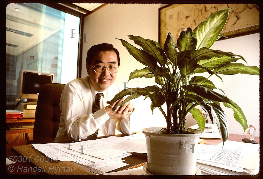Monsanto Far East Limted's Dennis Wan sits behind plant Feng Shui man said would deflect bad enrgy Hong Kong
