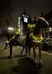 © Licensed to London News Pictures. 01/01/2021. London, UK. Mounted police try to disperse crowds gathering on New Year's Eve as Big Ben strikes midnight near Parliament in central London. Photo credit: Peter Macdiarmid/LNP