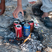 Syrian refugees using empty cans of coke to boil water for their tea in Kara Tepe camp