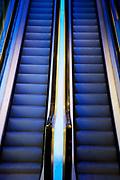 Up and down escalators lit up blue.