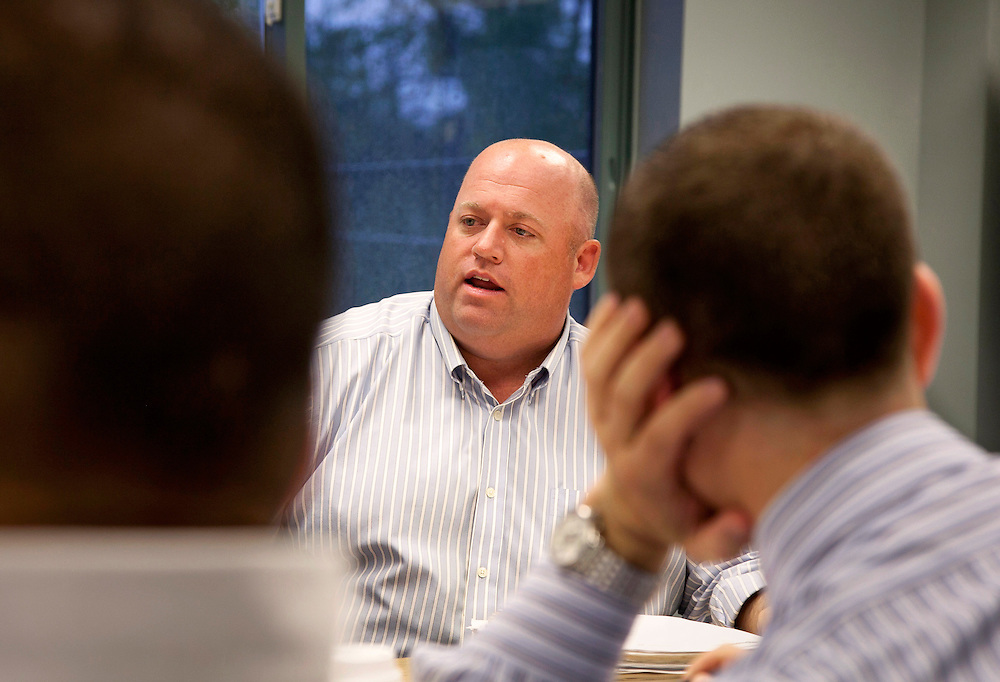 Man seen between two other men speaks during a small business meeting