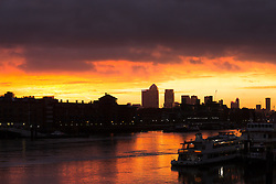 © Licensed to London News Pictures. 10/09/2016. LONDON, UK.  Pink sky and black clouds are seen during dawn sunrise on the River Thames this morning behind the Canary Wharf financial district. A spell of rain and wet weather is forecast for this weekend ahead of another mini heatwave next week.  Photo credit: Vickie Flores/LNP