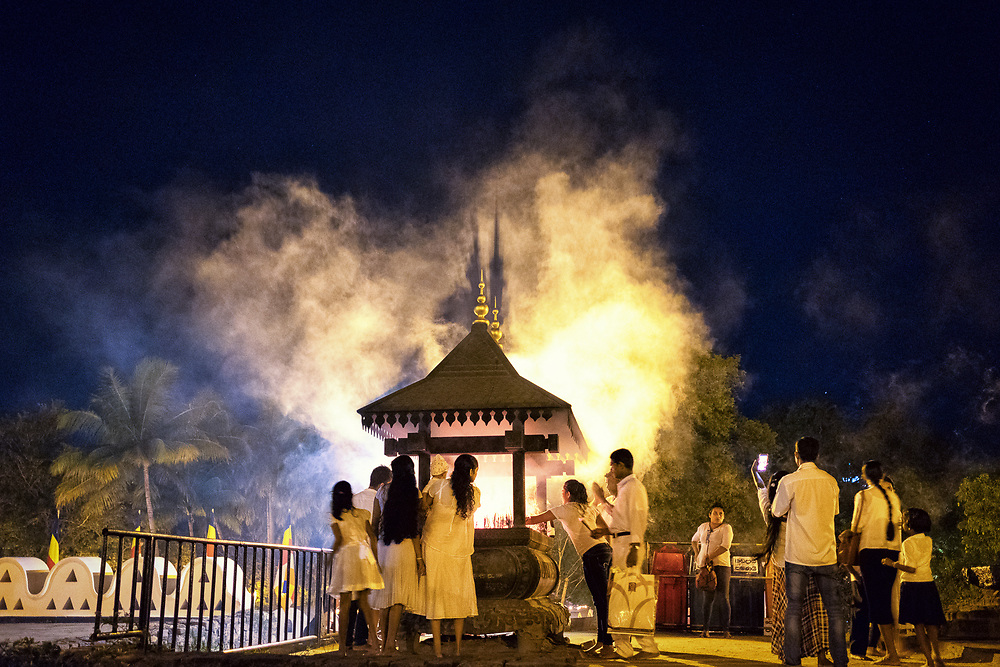 Buddhist pilgrims light incense inside the Temple of the Sacred Tooth Relic complex