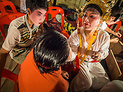 """06 DECEMBER 2015 - BANGKOK, THAILAND: Chinese opera performers put on their makeup before going on stage at the Ruby Goddess Shrine in the Dusit district of Bangkok. Chinese opera was once very popular in Thailand, where it is called """"Ngiew."""" It is usually performed in the Teochew language. Millions of Chinese emigrated to Thailand (then Siam) in the 18th and 19th centuries and brought their culture with them. Recently the popularity of ngiew has faded as people turn to performances of opera on DVD or movies. There are about 30 Chinese opera troupes left in Bangkok and its environs. They are especially busy during Chinese New Year and Chinese holidays when they travel from Chinese temple to Chinese temple performing on stages they put up in streets near the temple, sometimes sleeping on hammocks they sling under their stage.     PHOTO BY JACK KURTZ"""