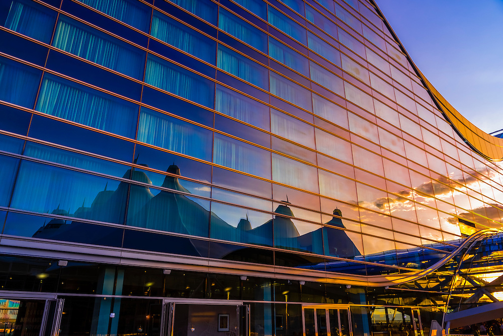 The tent like roof of the Jeppesen Terminal is reflected in the glass exterior of the Westin Denver International Airport Hotel,  Denver, Colorado USA.