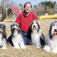 David Williamson poses with his four bearded collies, Max, left Harley Darby and Murray all male dogs, on the agility course in Pearland.  Williamson competes with all of his dogs on the course.