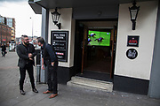 Street scene as men stand smoking outside the Bullring Tavern pub while the horse racing plays on a television inside in Birmingham, United Kingdom.