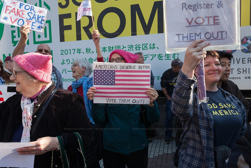 """A woman wears a pink pussy hat and holds a sign saying, Americans Deserve Better"""" at the Vote Out the Scandal rally at Hachiko Square, Shibuya, Tokyo, Japan. Sunday November 5th 2017. Timed to coincide with President Trumps visit to Japan, About 120 Americans living in Japan and some local Japanese  protested together from 2pm to 4pm to encourage US citizens to register to vote in future elections and call on the US government to honour it responsibilities to the American people,."""