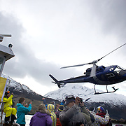 Athletes enjoy a Corona beer after competition as a helicopter flies past at the World Heli Challenge Extreme Day at Mount Albert on Minaret Station, Wanaka, New Zealand. 1st August 2011